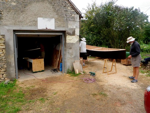 "Nice looking black hull of the ""Quick Canoe"" peeking around the corner of Brian's barn in France."