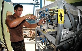 Navy diver checks the connection fittings to a surface supplied compressed air diving system