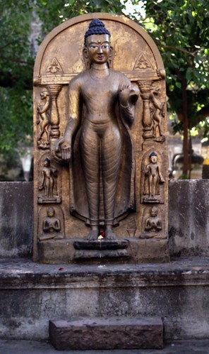 Gold painted concrete statue of standing Buddha in varada-mudrā mudra, holding his robes, with standing lions, 5 Buddhas, columns, offerings on lotus, near where Buddha gained enlightenment, BodhGaya, H.P., India in 1993 by Wonderlane