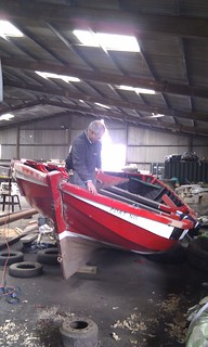 Mark Stockl of Ullapool, a boatbuilder makes repairs to the traditional dipping lugger, Jubilee. 2011.