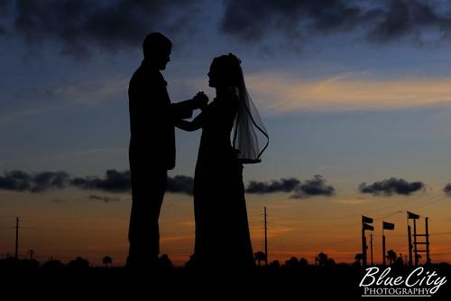 wedding sunset portrait sky orange silhouette clouds groom bride couple texas veil dress tx picture suit tuxedo romantic freeport riverplace lakejackson brazoriacounty bluecityphotography bluecityphotographycom