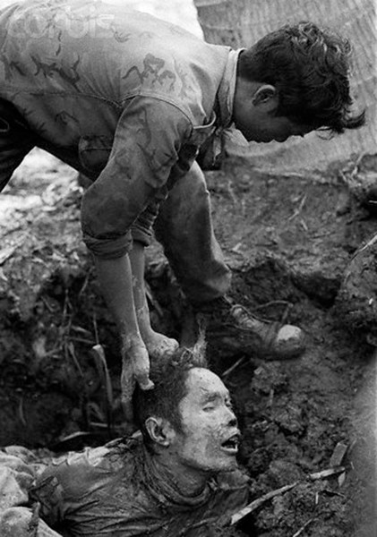 A soldier of the Army of the Republic of Vietnam handles a corpse, 1966, by Christian Simonpietri