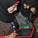 Two students from Bahrain check out a Facebook page on their iPad.