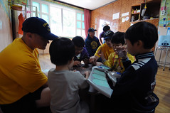 BUSAN (Oct. 2, 2011) USS George Washington (CVN 73) Sailors play Yu-Gi-Oh! with children at Sung Ae Won Home for Children during a community service project. (U.S. Navy photo by Mass Communication Specialist Seaman Alysia R. Hernandez)