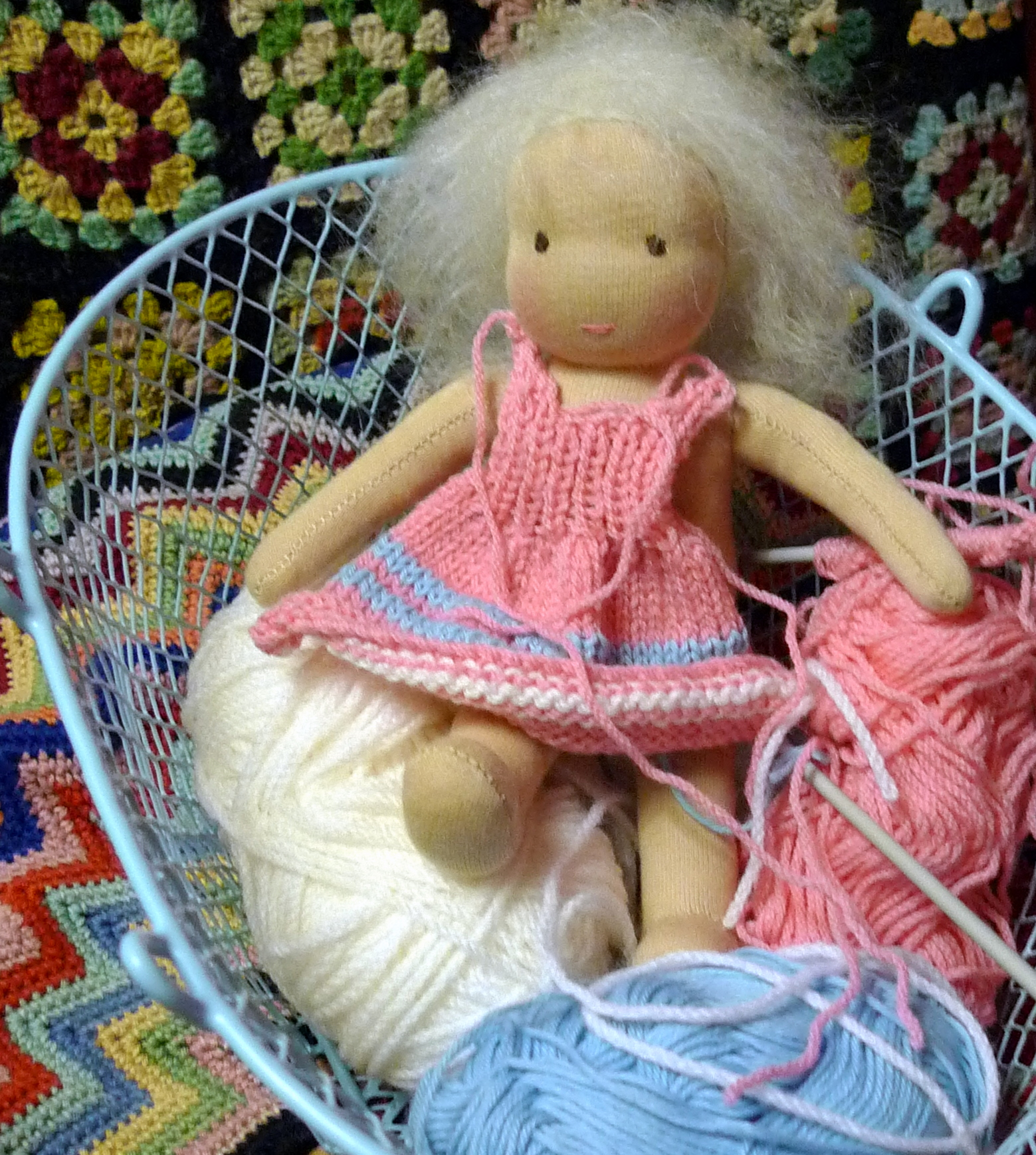 with her hair in eyes and her colour bleached out by the artificial light she waits for the knitter to finish her dress.