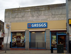 "A rather bleak-looking shop frontage constructed of weather-stained grey blocks. A shop sign reads ""GREGGS"" in large letters. The shop window is partly occupied by an advertisement and partly frosted glass. Street furniture clutters the pavement in front."