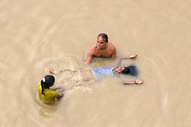 A family washing themselves in the Ganges river in Varanasi, India.