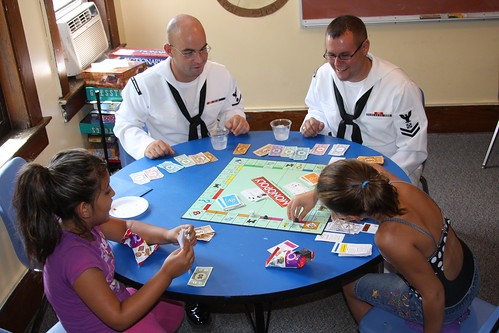 Sailors play board games with children at the Cameron Community Ministries during Rochester Navy Week