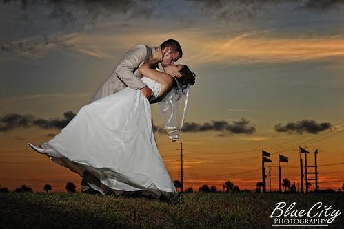 wedding sunset portrait sky orange clouds groom bride kiss couple texas veil dress tx picture suit tuxedo romantic freeport dip riverplace lakejackson brazoriacounty bluecityphotography bluecityphotographycom