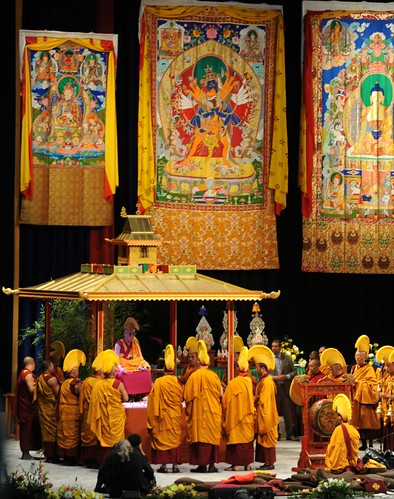 His Holiness Dalai Lama sitting on the Kalachakra mandala pavilion after dismantling the mandala, with his monks in orange robes and hats, thangkas of Padmasambhava, Kalachakra, and Lord Buddha, drum, torma offerings, Verizon Center, Washington D.C., USA by Wonderlane