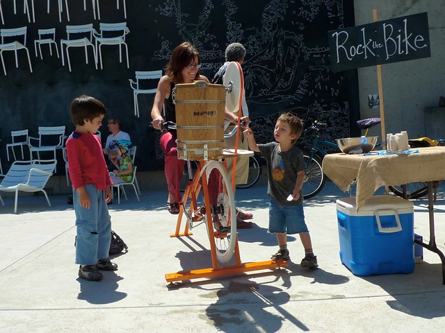 Kids try to figure out the mechanics of bike powered machine