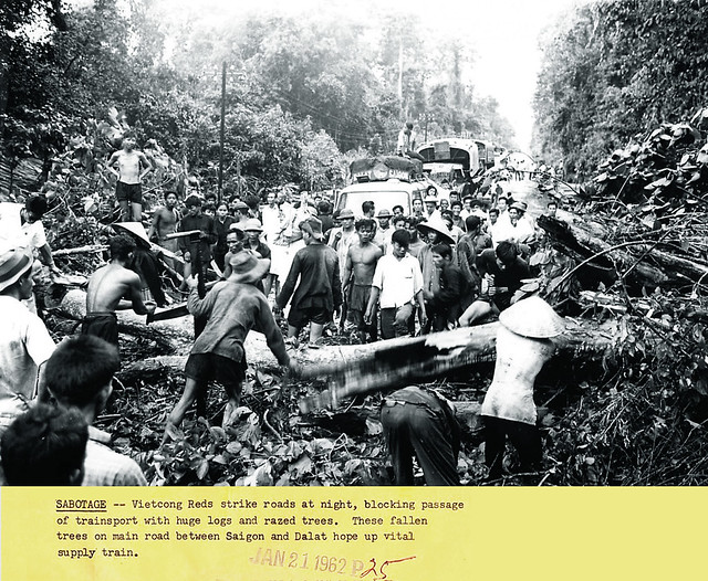 1962 - Civilians work to clear road block, caused by Viet Cong, on main road between Saigon and Dalat