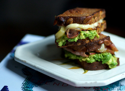 Grilled sandwich with avocado, cheese, bacon and an apple