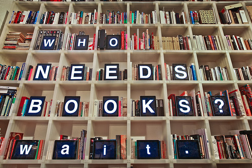 "Book shelf with a nook on each shelf spelling out words ""Who needs books?"""