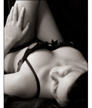 Bride-to-be poses for an sensuous boudoir photograph for her wedding night gift for him.
