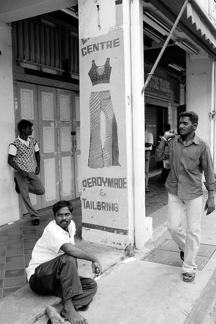 Migrant workers relaxing along the sidewalk at Little India.