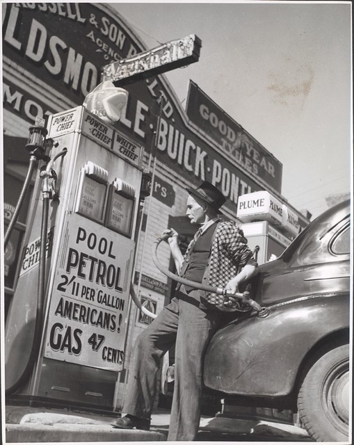 William Russell putting the four gallon monthly ration of petrol into a customer's car, Drouin, Victoria