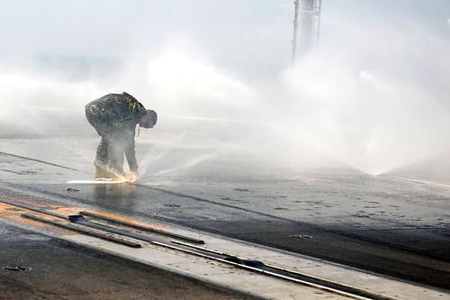 Sailor inspects a sprinkler on the flight deck