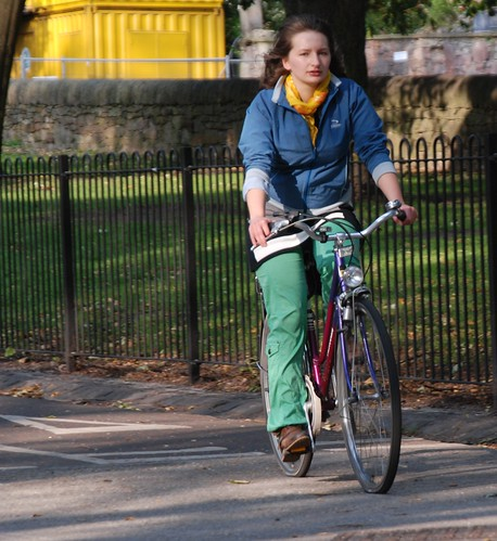 Yellow scarf, blue jacket, red bike