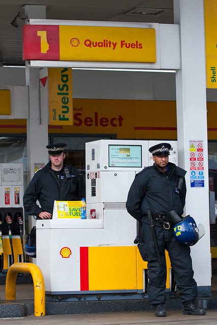 Police protecting the petrol pumps on Whitechapel Road, London
