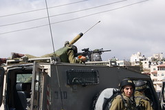 Soldier aims automatic rifle up main street of Beit Ommar