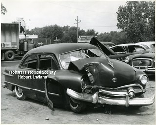 Black Cat behind wrecked car, no date