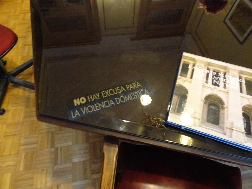 Sticker under the glass of Supreme Court Dep. Chief Justice's conference table: No Hay Excusa para la Violencia Familiar  - There's No Excuse for Domestic Violence.