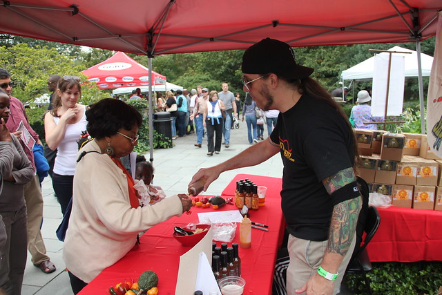 A visitor tastes a hot sauce sample. Photo by Rebecca Bullene.
