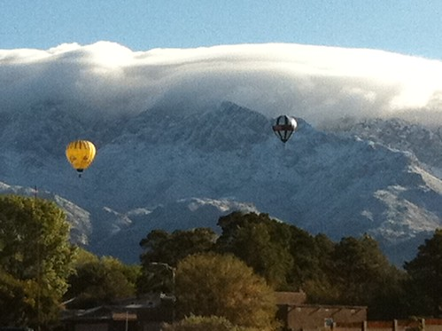 Balloon fiesta balloons float near the Sandia Mts.