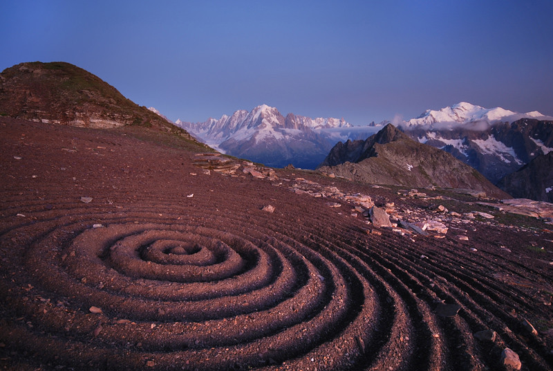 Photo of a land-art installation in the Swiss Alps. The earth has been manipulated to represent a set of concentric circles.