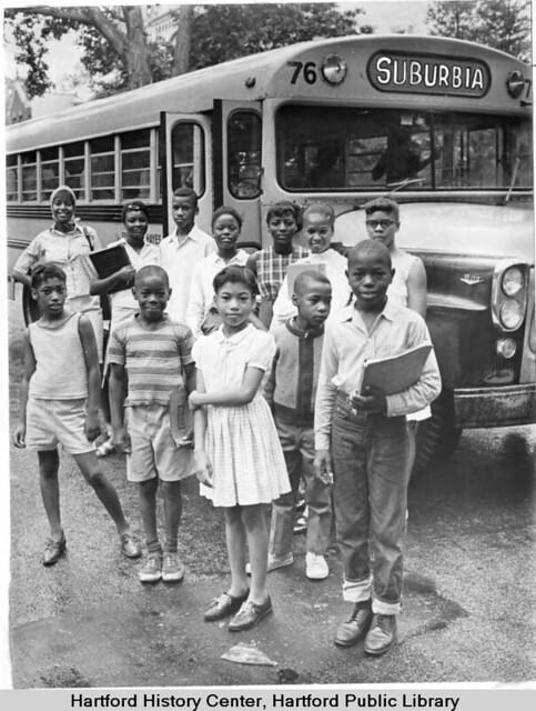 African American children in front of school bus