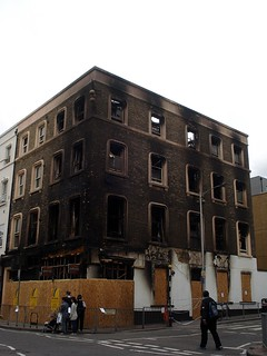 A four-storey building on the corner of two streets. The ground floor is boarded off. On the upper floors, glass is missing from the windows and extensive scorching is visible on the brickwork.