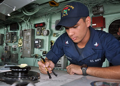 In this file photo, Quartermaster 3rd Class Scott McCutcheon plots the ship's current position in the pilothouse of the amphibious transport dock USS Denver (LPD 9), Aug. 13, 2011.  (U.S. Navy photo by Mass Communication Specialist 2nd Class Bryan Blair)