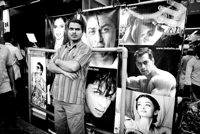 A man in front of many posters - only in Little India.