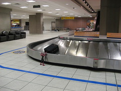 Spider-Man getting his bag from the luggage carousel