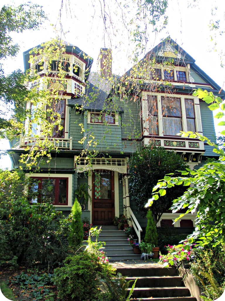 beautiful green queen anne victorian house with turret a photo