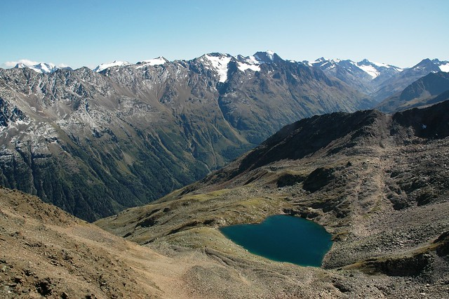 Hiking in Oetztal: A heart-shaped little lake amidst tall snow-capped mountains in Oetztal, in the Austrian region of Tyrol.