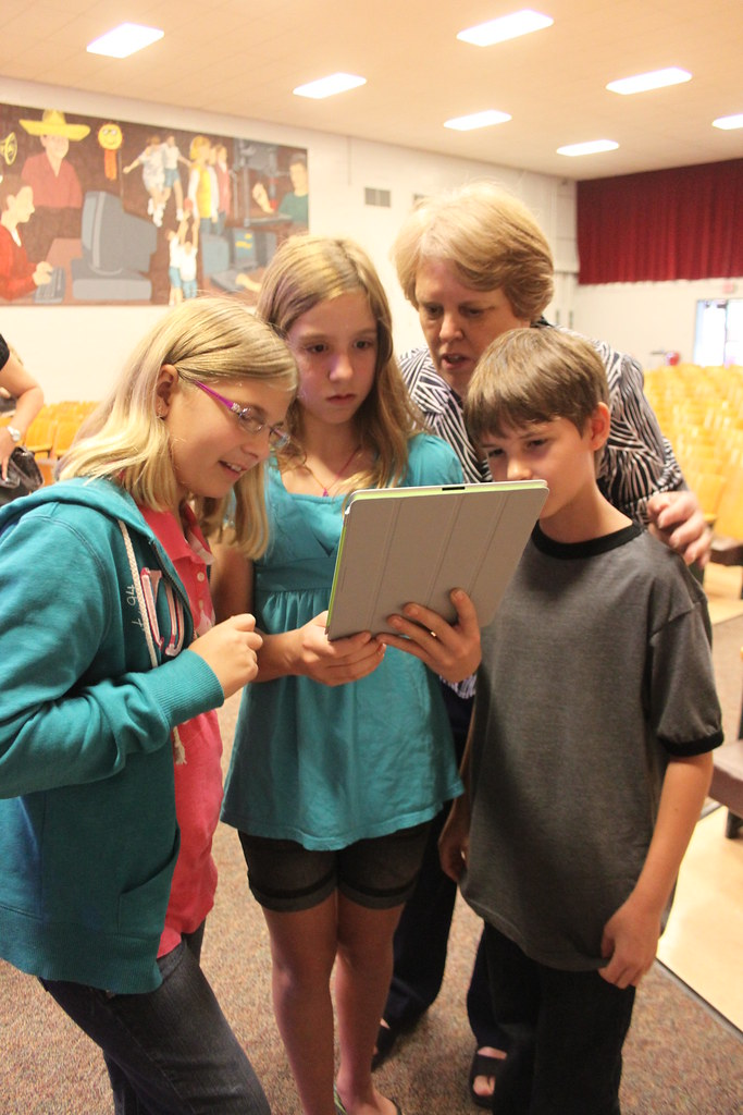 students gather around their teacher's ipad