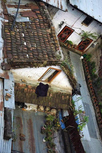 Rooftop porches of local abodes, potted plants, aluminum panels, tile roof, doors, windows, fabrics, Boudha, Kathmandu, Nepal by Wonderlane