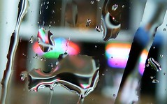 Drops of water reflecting neon light as they fall on a flat glass
