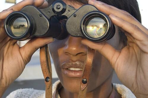 woman using binoculars to scan the horizon