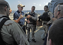 In this file photo, Lt. j.g. Jason Dawson, a visit, board, search, and seizure (VBSS) boat officer aboard USS Dewey (DDG 105) debriefs his team following a VBSS training event in the South China Sea, Sept. 13, 2011. (U.S. photo by Mass Communication Specialist 3rd Class Joshua Keim)