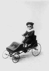 Child driving a toy car by State Library of Queensland, Australia