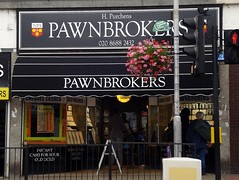 "A small terraced shopfront signed in white letters on a black background: ""H. Purchens / PAWNBROKERS / 020 8688 2432 / PAWNBROKERS"". The windows carry a display of jewellery, and some passers-by have stopped for a look. A globular hanging-basket display of pink and red flowers hangs from a lamp-post in the foreground."