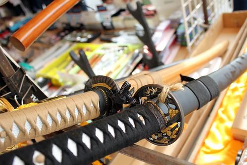 """Primero vamos a ver qué es exactamente un shinken. El término quiere decir literalmente """"espada real"""": llamamos shinken a toda katana forjada (dentro o fuera de Japón) de buena calidad. Aunque shinken es el nombre que más se utiliza para referirnos a katana real, la katana que empleamos en práctica de corte, los japoneses tienen todavía más clasificaciones:  Kazarito: Aunque lo vendan afilado no es un shinken. Son katanas ornamentales, que podemos comprar como souvenirs en cualquier armería o incluso en bazares chinos. Generalmente la tsuka suele ser de plástico y con formas muy horteras barrocas: cobras y dragones. No sirven para entrenar: sólo decoración.  Modoki: Una forma de llamar a los shinken de muy buena calidad forjados fuera de Japón. Por ejemplo, una WKC o una Hanwei serían modoki: hojas realmente buenas pero, para los japoneses, faltas de pedigree.  Shinsakuto: Shinken de muy buena calidad forjado en Japón recientemente. Si queremos uno, tenemos que saber que vienen con documentos del gobierno japonés y del registro oficial de armeros; y eso se paga.  Nihonto: Espada forjada antes del año 1900. El término nihonto se aplica tambien para cualquier katana auténtica, con pedigrí; pero normalmente es el denominador de la katana antigua.  Estas son las definiciones más comunes para los shinken o katanas que encontraremos por ahí. Cuando hablamos de koshirae nos referimos al estilo: para ser breves, los motivos que decoran la tsuba, el kashira o incluso el trenzado de la tsuka. Pero, como decíamos al principio, nunca ha de ser lo más importante."""