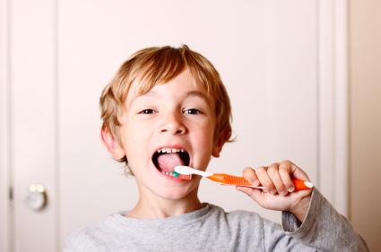 Boy brushing teeth with fresh tasting toothpaste.