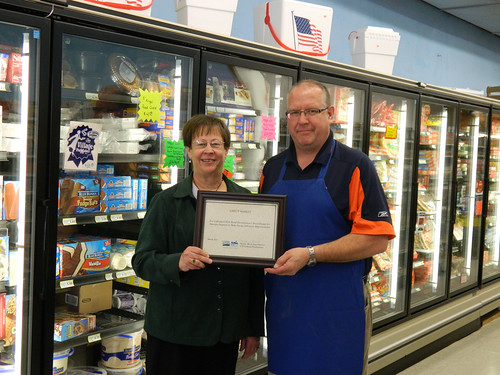 Greg Yound of Greg's Market in Exeter accepts certificate from State Director Maxine Moul for the new freezers resulting from an energy efficiency grant.