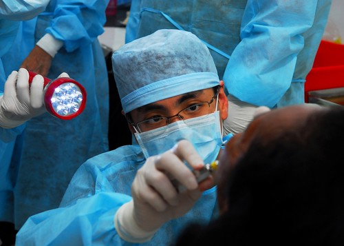 Singapore Military Force Capt. (Dr.) Desmond Ng performs a tooth extraction during a dental civic