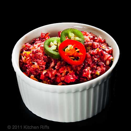 Cranberry Jalapeno Relish in white ramekin on black background, jalapeno slice garnish
