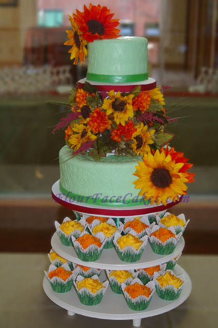 Tuscan Sun Wedding Cake 2 tier cake separated by an arrangement of bright